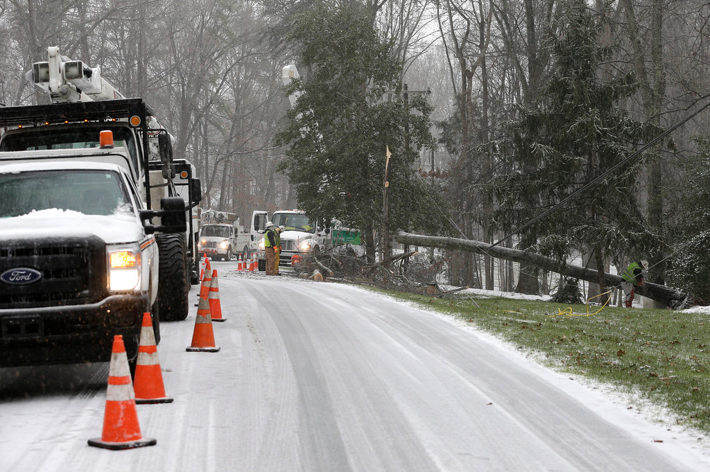. Duke Energy employees work to restore power in a neighborhood in Matthews, N.C., Friday, Jan. 22, 2016. A massive blizzard began dumping snow on the southern and eastern United States on Friday, with mass flight cancellations, five states declaring states of emergency and more than 2 feet (60 centimeters) predicted for Washington alone. (AP Photo/Chuck Burton)