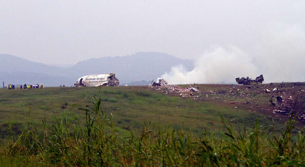 . Debris burns as a UPS cargo plane lies on a hill at Birmingham-Shuttlesworth International Airport after crashing on approach, Wednesday, Aug. 14,  2013, in Birmingham, Ala. (AP Photo/Butch Dill)