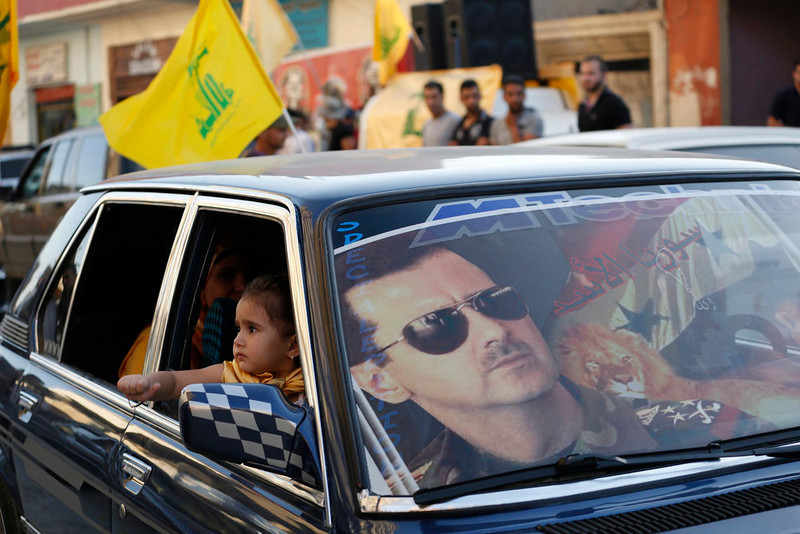 . An image of Syria\'s President Bashar al-Assad is seen on a car\'s windscreen as Hezbollah supporters celebrate, after the Syrian army took control of Qusair from rebel fighters, in the Shi\'ite town of Hermel June 5, 2013. Syrian government forces and their Lebanese Hezbollah allies seized control of the border town of Qusair on Wednesday, dealing a major defeat to rebel fighters battling to overthrow Assad. REUTERS/Jamal Saidi