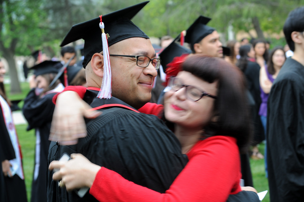 . Cinema and Television Arts major Mike Magana gets a hug from his wife Jennifer Magana before the CSUN commencement ceremony, Tuesday, May 21, 2013. (Michael Owen Baker/L.A. Daily News)