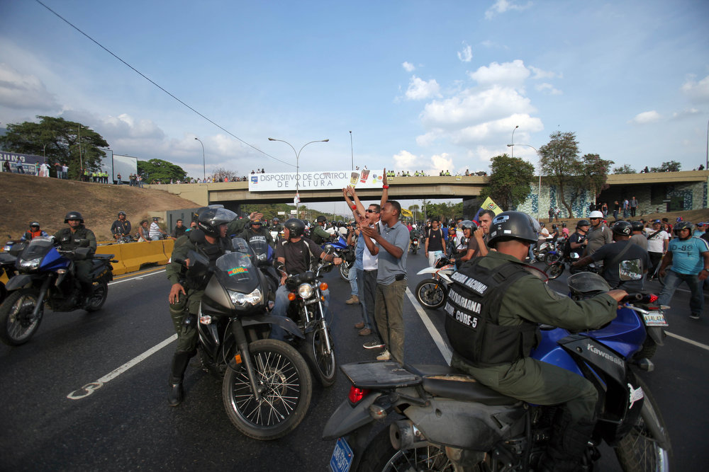 . National Guard soldiers on motorcycles surround demonstrators as opposition supporters and students block a highway in the Altamira neighborhood in Caracas, Venezuela, Monday, April 15, 2013. National Guard troops fired tear gas and plastic bullets to disperse students protesting the official results in Venezuela\'s disputed presidential election.(AP Photo/Fernando Llano)