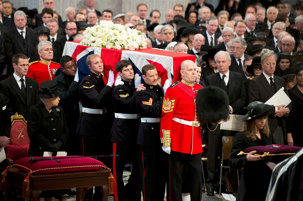 . Britain\'s Queen Elizabeth (front L) and Mark Thatcher (R), son of former British prime minister Margaret Thatcher, watch as her coffin arrives in St Paul\'s Cathedral for the funeral service, in London April 17, 2013. Thatcher, who was Conservative prime minister between 1979 and 1990, died on April 8 at the age of 87.    REUTERS/Paul Edwards/Pool