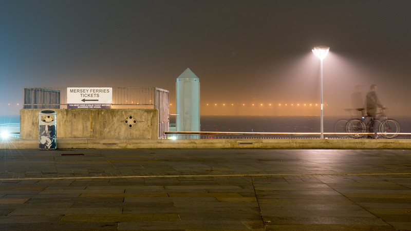 Cyclist beside the Mersey in the fog