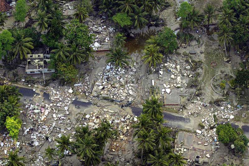 . An aerial shot taken from a helicopter shows debris of houses destroyed by tsunamis on both sides of a road in the Galle district in the southwestern coast of Sri Lanka, 27 December 2004.  Sri Lanka launched a massive humanitarian operation 27 December after tsunamis devastated much of the island\'s coastline, killing at least 5,860 people of which 70 were foreign tourists, while 1,555 others are reported missing.          JIMIN LAI/AFP/Getty Images