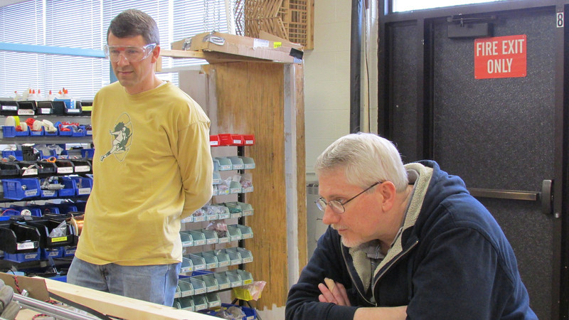 Mr. Hoggatt and Mr. Dickinson watch as Mechanical works busily.