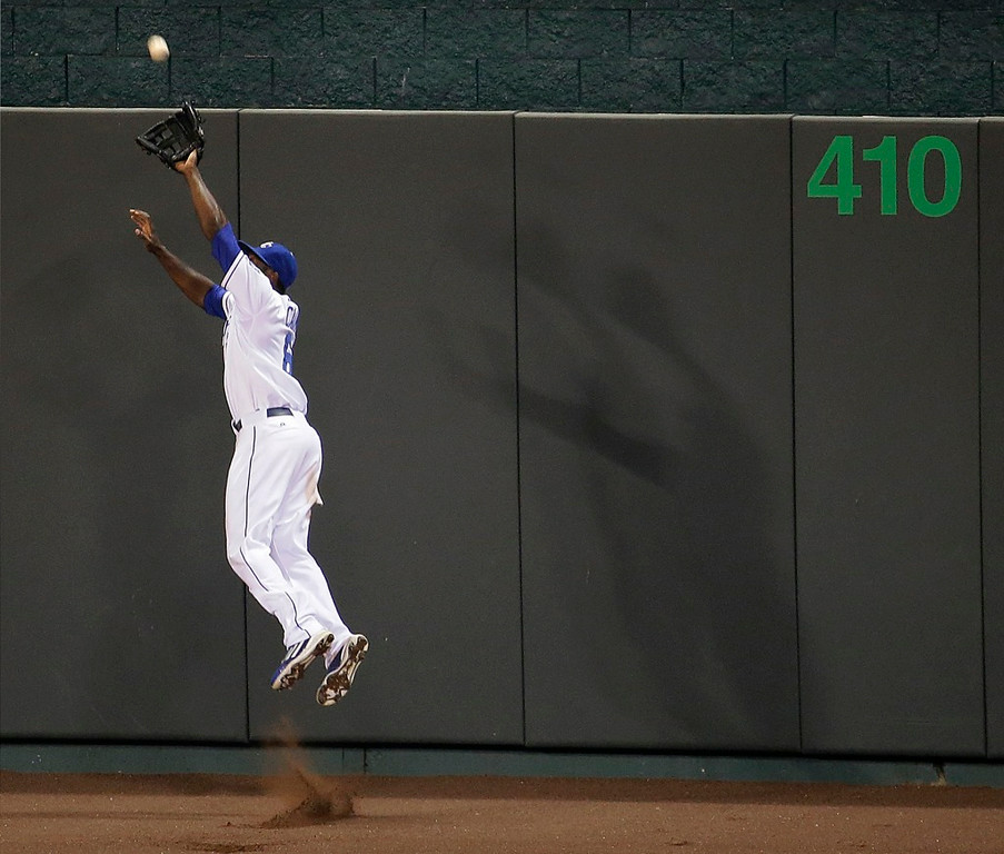 . Royals center fielder Lorenzo Cain leaves his feet to catch a deep fly from Minnesota\'s Oswaldo Arcia at the wall  during the seventh inning. (AP Photo/Charlie Riedel)