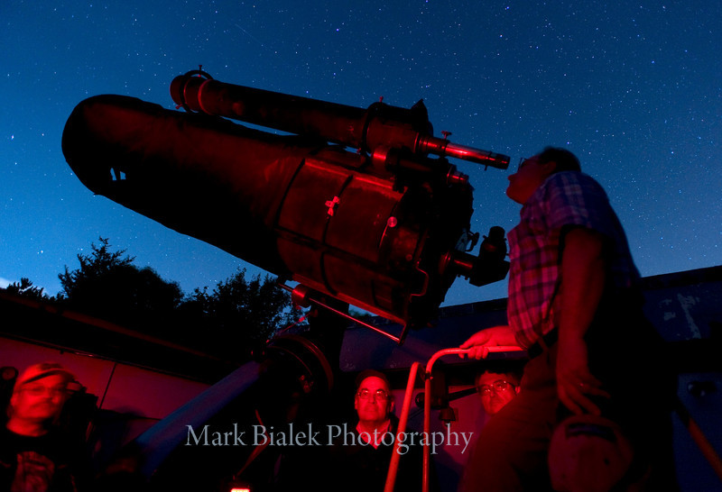 "Tom Ryan of Ann Arbor looks through the 24"" Cassegrain telescope at Peach Mountain near Dexter.  (Photo by Mark Bialek)"