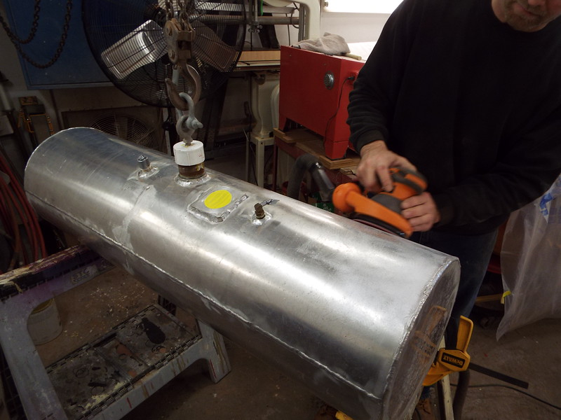 Sanding the fuel tank to prep it for paint.
