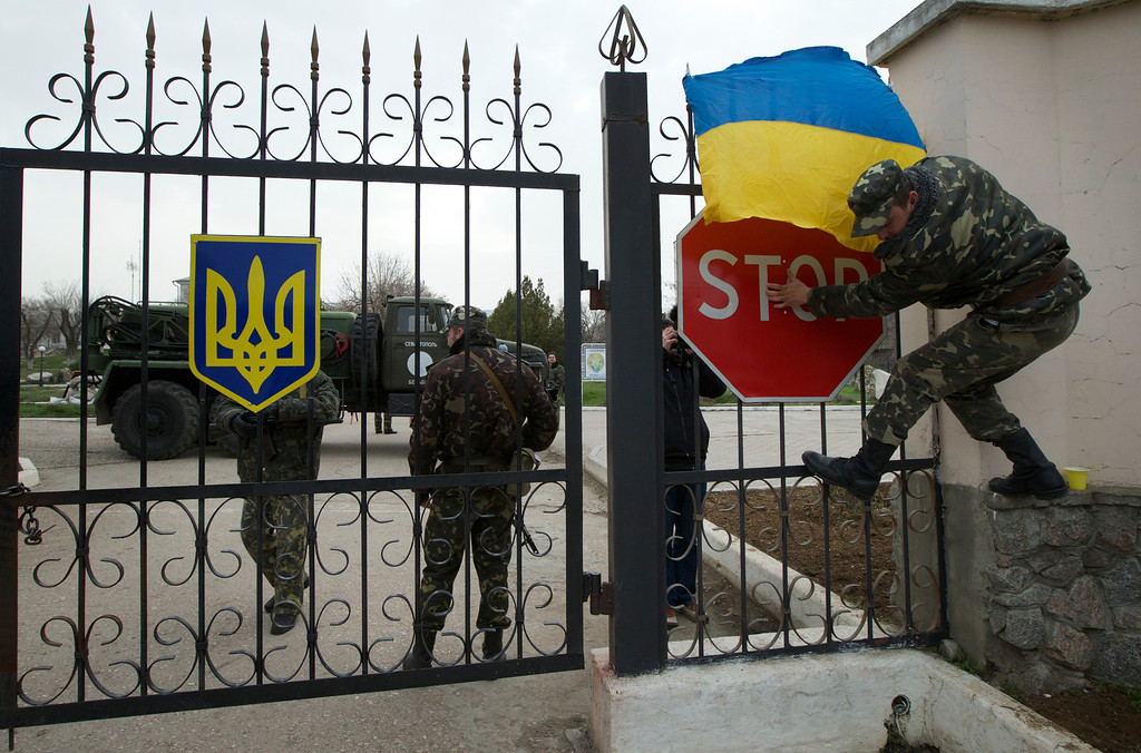 . A Ukrainian airman puts the national flag over the gate as they guard what\'s left under their control at the Belbek air base, outside Sevastopol, Ukraine, on Tuesday, March 4, 2014. Russian troops, who had taken control over Belbek airbase, fired warning shots in the air as around 300 Ukrainian officers marched towards them to demand their jobs back. (AP Photo/Ivan Sekretarev)