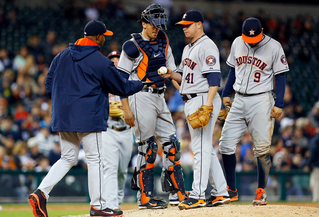 . Houston Astros manager Bo Porter, left, takes the ball from Houston Astros pitcher Brad Peacock (41) against the Detroit Tigers in the seventh inning of a baseball game in Detroit, Wednesday, May 7, 2014. (AP Photo/Paul Sancya)