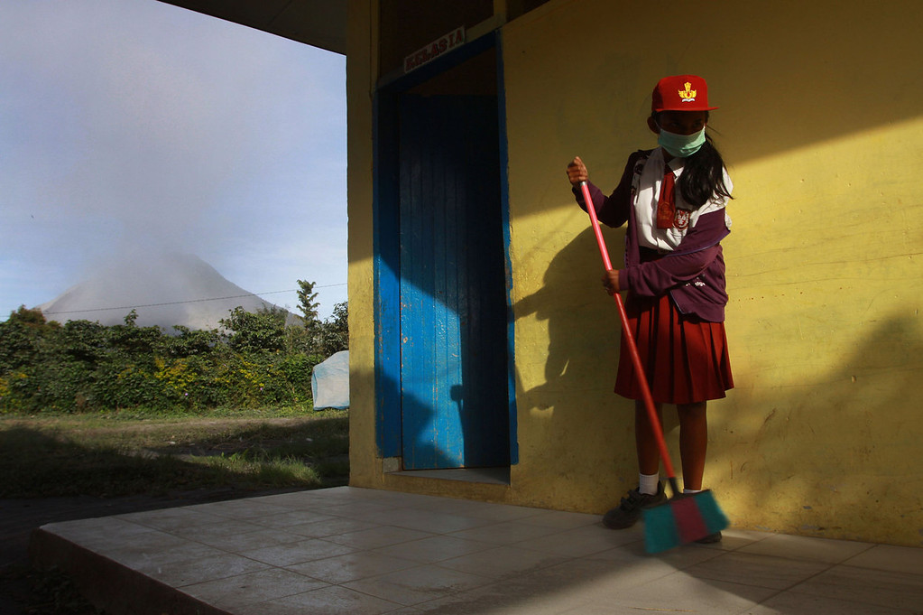 . An Indonesian student sweeps volcanic ash from the school hallway in Karo district on September 16, 2013 while Mount Sinabung volcano (L) emits steam and ash.  Thousands of villagers fled on September 15, 2013 after Sinabung erupted on Indonesia\'s Sumatra island spewing rocks and red-hot ash onto surrounding villages, officials said.  The volcano was dormant for nearly 100 years before erupting in August and September 2010, forcing about 12,000 people to flee.    KHARISMA TARIGAN/AFP/Getty Images