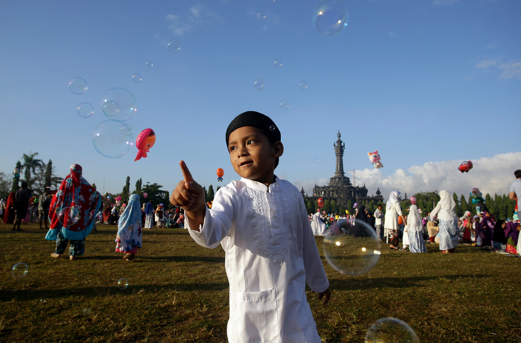 . A Muslim boy plays with bubbles as he attends Eid al-Fitr prayers to mark the end of the holy fasting month of Ramadan in Bali, Indonesia, Friday, June 15, 2018. (AP Photo/Firdia Lisnawati)