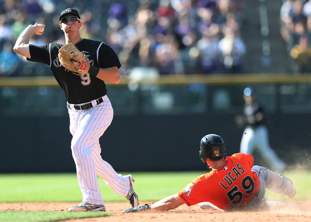. Colorado Rockies second baseman DJ LeMahieu, left, turns to throw after forcing out Miami Marlins\' Ed Lucas, right, at second base on the front end of a double play hit into by Adeiny Hechavarria in the eighth inning of the Rockies\' 7-4 victory in a baseball game in Denver, Sunday, Aug. 24, 2014. (AP Photo/David Zalubowski)