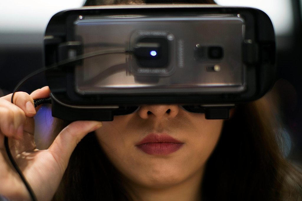 . A visitor looks through a VR gear installed on a new Samsung Galaxy S9 mobile phone, during the Mobile World Congress wireless show, in Barcelona, Spain, Monday, Feb 26, 2018. The annual Mobile World Congress (MWC) runs from 26 February - 1 March and draws over 2,300 exhibitors to Barcelona, including industry heavyweights Samsung, Huawei and Nokia. (AP Photo/Emilio Morenatti)