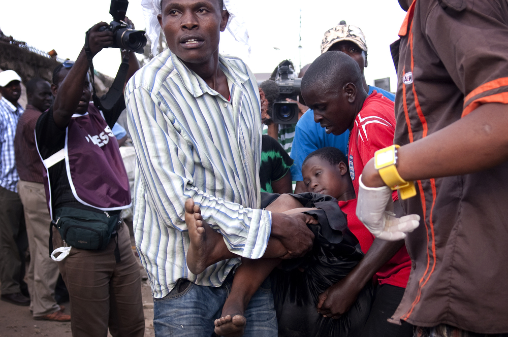 . A victim is carried to an ambulance after two improvised explosive devices (IED) went off in Gikomba market on May 16, 2014 in Nairobi, Kenya. Two improvised explosive devices (IED) were activated, killing several people and injuring more than 70. One person has been apprehended as a suspect in the attack. (Photo by Christena Dowsett/Getty Images)