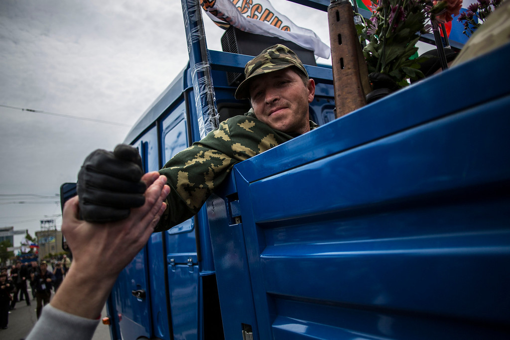 . A pro-Russia man shakes hands with a pro-Russian activist while leaving the commemoration of Victory Day in Donetsk, Ukraine, Friday, May 9, 2014. Victory Day honors the armed forces and the millions who died in World War II. This year it comes as Russia is locked in the worst crisis with the West, over Ukraine, since the end of the Cold War. (AP Photo/Manu Brabo)