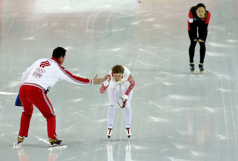 . Russia\'s Olga Fatkulina greets her coach as China\'s Wang Beixing catches her breath after their first heat in the women\'s 500-meter speed skating race at the Adler Arena Skating Center during the 2014 Winter Olympics, Tuesday, Feb. 11, 2014, in Sochi, Russia. (AP Photo/David J. Phillip )