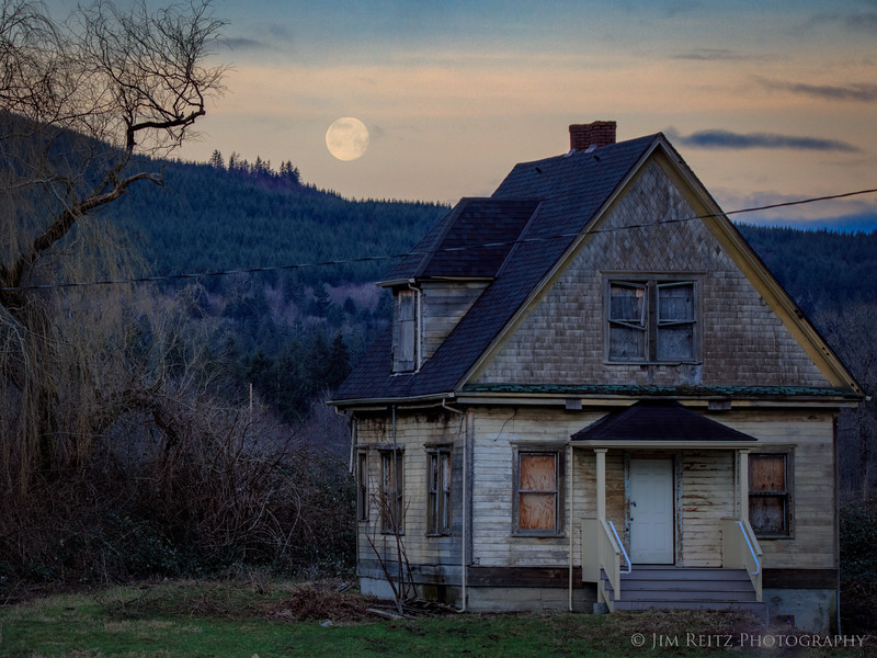 Moonrise behind an abandoned farm house at Tollgate Farm park in North Bend, Washington