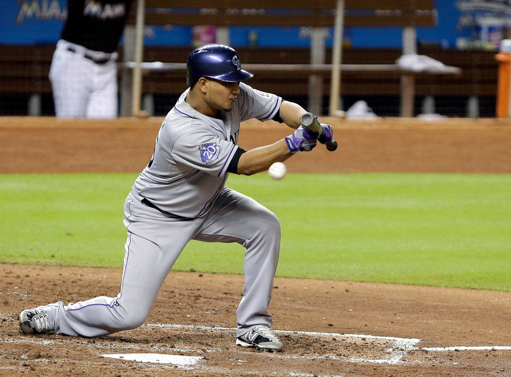 . Colorado Rockies\' Jhoulys Chacin attempts a bunt during the fifth inning of a baseball game against the Miami Marlins, Friday, Aug. 23, 2013, in Miami. (AP Photo/Wilfredo Lee)