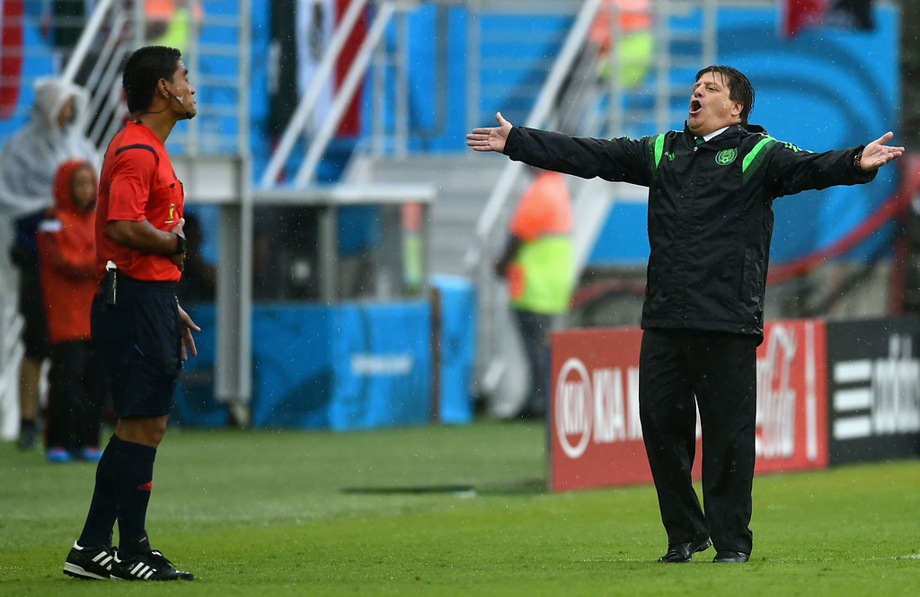 . Head coach Miguel Herrera of Mexico reacts toward fourth official Norbert Hauata during the 2014 FIFA World Cup Brazil Group A match between Mexico and Cameroon at Estadio das Dunas on June 13, 2014 in Natal, Brazil.  (Photo by Matthias Hangst/Getty Images)