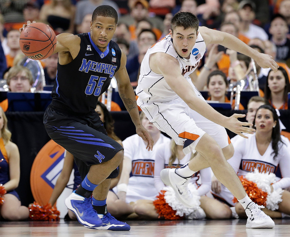 . Memphis guard Geron Johnson (55) moves the ball against Virginia forward/center Mike Tobey (10) during the second half of an NCAA college basketball third-round tournament game, Sunday, March 23, 2014, in Raleigh, N.C. (AP Photo/Gerry Broome)