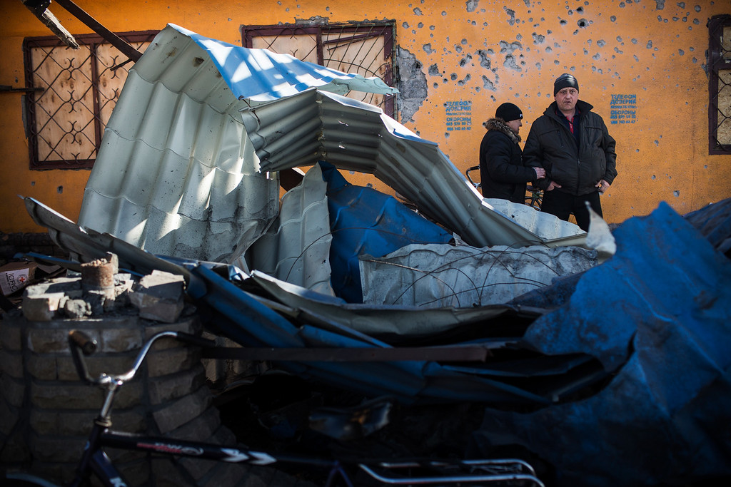 . DEBALTSEVE, UKRAINE - FEBRUARY 25:  Men survey damage created by fighting between Russian backed rebels and Ukrainian soldiers on February 25, 2015 in Debaltseve, Ukraine. After approximately one month of fighting, Russian backed rebels successfully forced Ukrainian troops to withdraw from the town of 100,00 people on February 18. Only approximately 11,000 civilians remain in the town. Debaltseve is considered an asset to both Ukrainians and the rebels due to the railway station and it\'s connection to other eastern Ukranian towns.  (Photo by Andrew Burton/Getty Images)