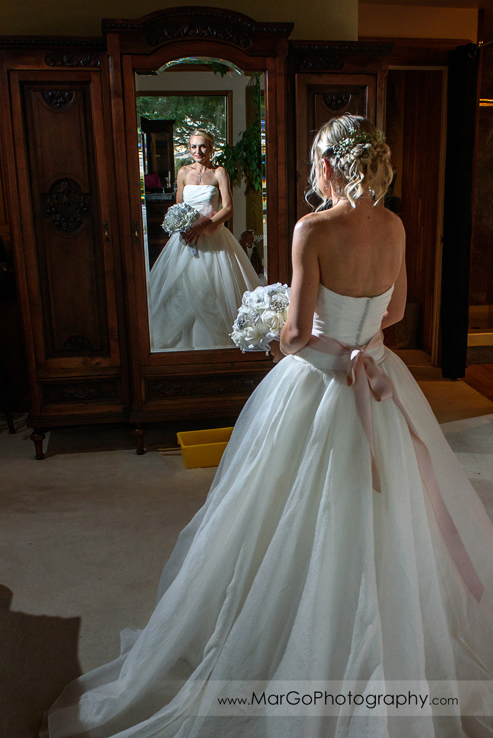mirror portrait of the bride in white wedding dress holding the bouquet
