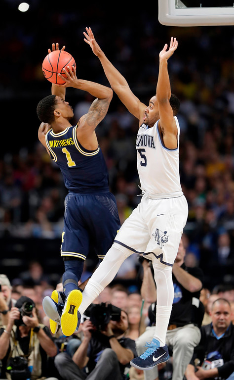 . Michigan\'s Charles Matthews (1) shoots against Villanova\'s Phil Booth (5) during the first half in the championship game of the Final Four NCAA college basketball tournament, Monday, April 2, 2018, in San Antonio. (AP Photo/Eric Gay)