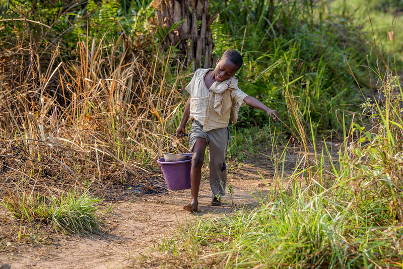 """Grace Mukoma, 10 yr-old boy, makes the long trek to collect water from a polluted swamp near his home in Kananga, Central Kasai Province, DRC.  Water Every day, Grace follows a winding, dirt path behind his house for about a mile. It leads downhill to a muddy pond. The water is brown and has a filmy covering on it. Grace rolls up his pants and wades in with a small, purple bucket which he fills up with a smaller, stainless steel bowl.  When the bucket is full, Grace struggles to carry it uphill eventually putting it on his head. He doesn't spill a drop.    """"I get water from the stream as many as 4 or 5 times a day. The walk takes around 1 hour both ways. The water is not good. Sometimes I get sick from it.""""  Background Grace lives with his mom, Mbombo Elize, sister Harriet, 7, and an extended family of relatives, including his grandmother, Kapinga Godelive, 66.  Mbombo has had 4 children, the first when she was 15. 2 died during the time they had to run away because of the war. Now it's just Grace and his sister Harriet, 7.  They live in the Kasai Centrale province in a place called Katoka. It's a rural community. Grace and his family had to run when war broke out in the DRC.  His father was killed. His mother and her 4 children ran about 2 kilometers down the road from his house towards the Lualua River. They hid there for about 3 months. Unfortunately, because of a lack of food and disease, Grace's brother and a sister died. After about 3 months Grace and his family hesitantly made their way back to their house. It had been burnt and was empty. They've struggled ever since.    Here's a look at Grace's life today:  Home Life  """"Early in the morning I sweep the compound. Then I wash and if there is food I eat. Then I join my friends at the CFS."""" """"Sometimes they send me on other errands. If they need something, they send me.""""  Food Grace's family doesn't have enough food. On any given day they may or may not eat. When they do eat, it's once a day, usually in the eveni"""
