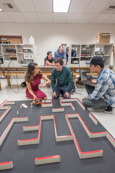 Students Melissa Renteria, 24, Daniel Wheeler, 21, AJ Dizon, 19, (front, left to right), Mason Landrum, 27, Matt Hardenburgh, 24, and John Robertson, 21 (back, left to right) in the Institute of Electrical and Electronic Engineers (IEEE) group work on their micro mouse project in the senior projects room on Thursday, April 27, 2017 in Chico, Calif. Micromouse is actually a miniature Robot controlled by a Microcontroller. The mouse has to find its way through an arbitrary maze. (Jason Halley/University Photographer)