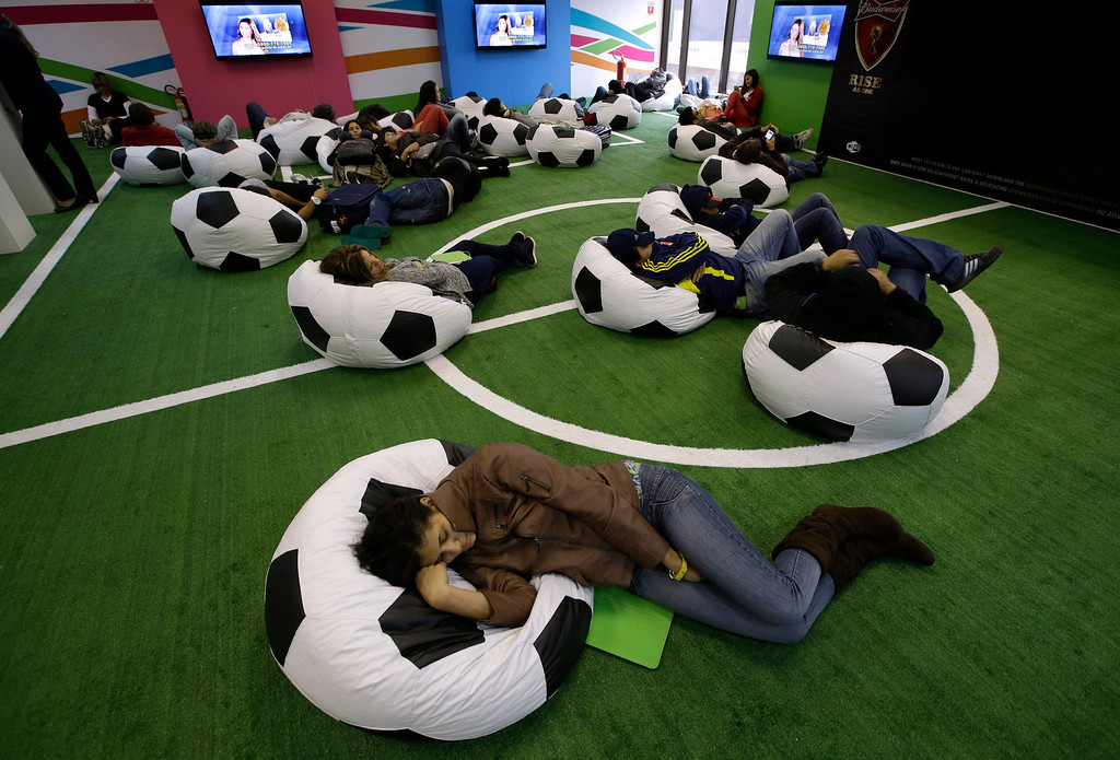 . Passengers rest on beanbags decorated like soccer balls as they wait for their flights ahead of the World Cup at the Guarulhos international airport in Sao Paulo, Brazil, Tuesday, June 10, 2014. The international tournament starts on June 12. (AP Photo/Lee Jin-man)