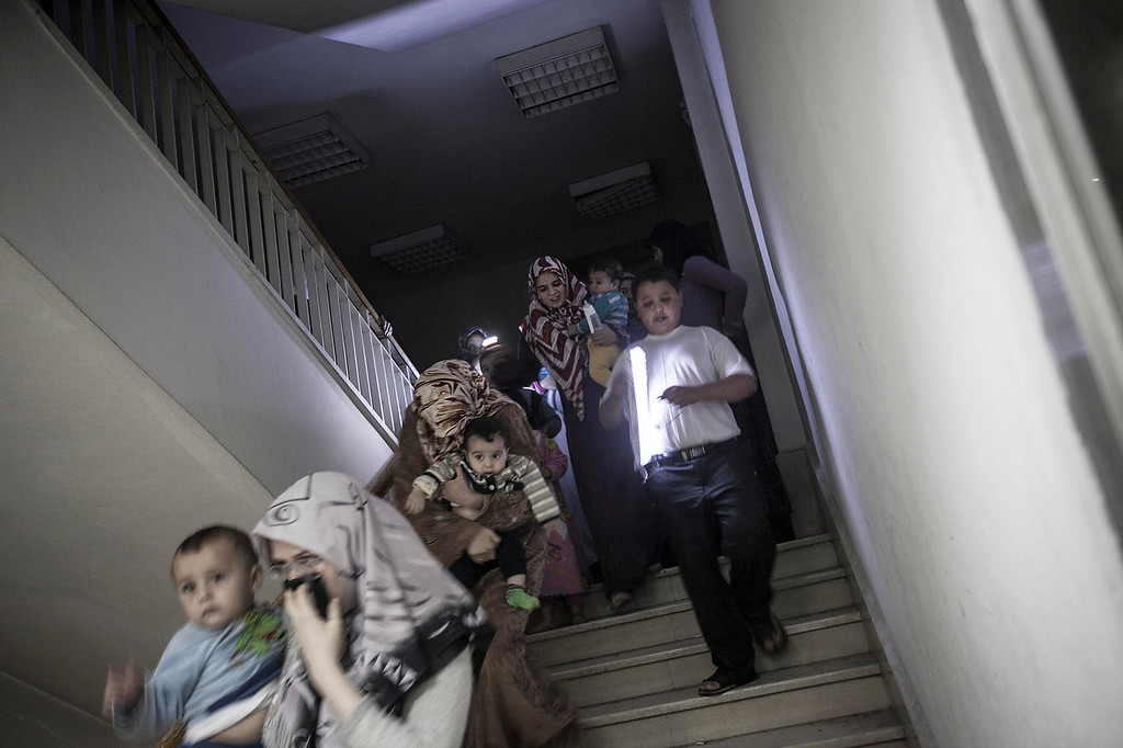 . In this Friday, Nov. 02, 2012 photo, Syrian residents run for cover to an underground basement as an attack by Syrian army heavy artillery hits an apartment compound of rebel fighter\'s families in Aleppo, Syria. U.N. officials and human rights groups believe President Bashar Assad\'s regime is responsible for the bulk of suspected war crimes in Syria\'s 19-month-old conflict, which began as a largely peaceful uprising but has transformed into a brutal civil war.  However a video that appears to show a unit of Syrian rebels kicking terrified, captured soldiers and then executing them with machine guns raised concerns Friday about rebel brutality at a time when the United States is making its strongest push yet to forge an opposition movement it can work with. (AP Photo/Narciso Contreras)
