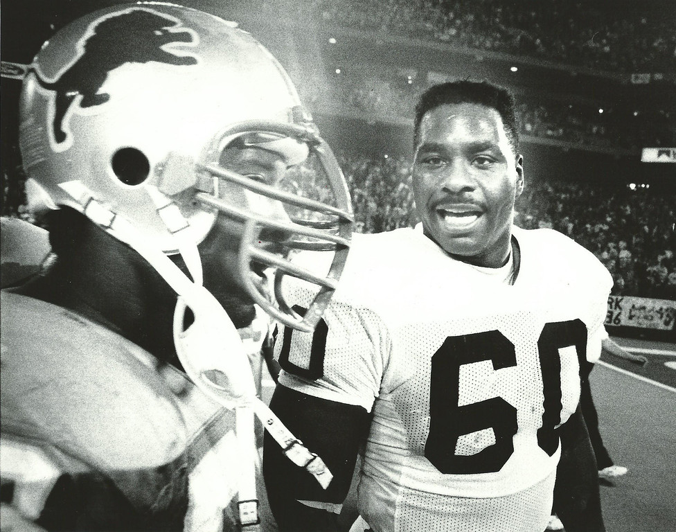 . Former Detroit Lions player Reggie Rogers (right) talks to a teammate in Nov. 1989. Oakland Press file photo