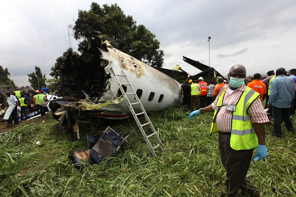 . Rescue workers inspect the wreckage of a charter passenger jet which crashed soon after take off from Lagos airport, Nigeria, Thursday, Oct. 3, 2013. (AP Photo/Sunday Alamba)