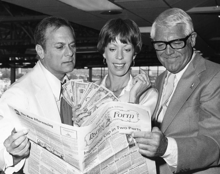 . Tony Curtis, Carol Burnett and Cary Grant enjoying themselves at Hollywood Park in May 1978. They are holding a Racing Form paper and money.   (Los Angeles Public Library)