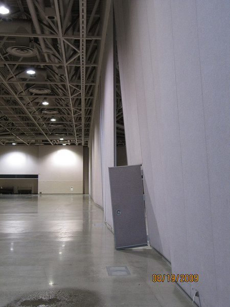 A large section of a wall was moved due to a sudden difference in air pressure. Water is seen lower left from damage to the convention center roof.