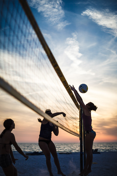 Woman playing volleyball on the beach.