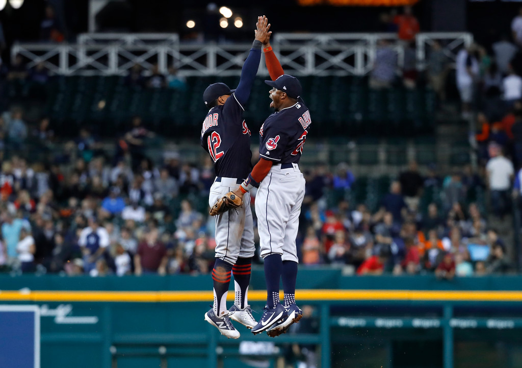 . Cleveland Indians shortstop Francisco Lindor (12) and center fielder Rajai Davis (26) celebrate after defeating the Detroit Tigers in a baseball game in Detroit, Friday, July 27, 2018. (AP Photo/Paul Sancya)