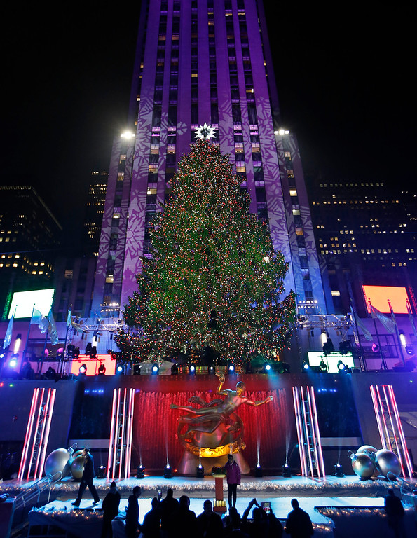 . A young woman stands at a podium that was used to light the Rockefeller Center Christmas tree as others take photographs of the tree, Wednesday, Dec. 4, 2013, in New York. Some 45,000 energy efficient LED lights adorn the 76-foot tree. (AP Photo/Kathy Willens)