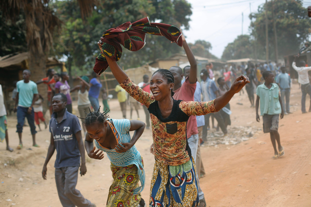 . Christian residents celebrate as Seleka Muslim militias evacuate the Kasai camp in Bangui, Central African Republic, Tuesday Jan. 28, 2014, to relocate and join other Selekas at the PK11camp. The departure of the fighters was greeted with screams of joy from the crowd of hundreds that gathered to watch them leave for another camp in northern Bangui. �We are free! This is our new year!� they shouted. Seleka became deeply unpopular after they killed and tortured civilians after seizing power in March 2013. Their leader Michel Djotodia stepped down as president earlier this month and went into exile in Benin. (AP Photo/Jerome Delay)