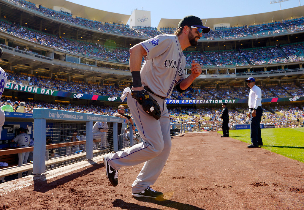 . Colorado Rockies first baseman Todd Helton runs out to his position during the first inning of the Rockies\' baseball game against the Los Angeles Dodgers, Sunday, Sept. 29, 2013, in Los Angeles. Helton is retiring after the season. (AP Photo/Mark J. Terrill)
