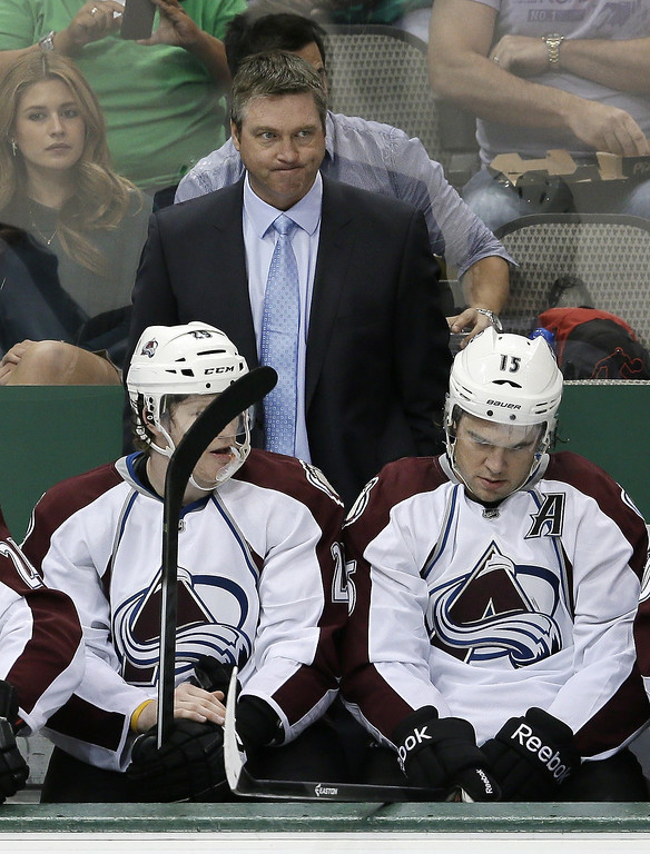 . Colorado Avalanche head coach Patrick Roy, center top, Nathan MacKinnon (29) and P.A. Parenteau (15) watch after the Dallas Stars scored one of their three goals in the third period of a preseason NHL hockey game on Thursday, Sept. 26, 2013, in Dallas. The Stars won 5-1. (AP Photo/Tony Gutierrez)