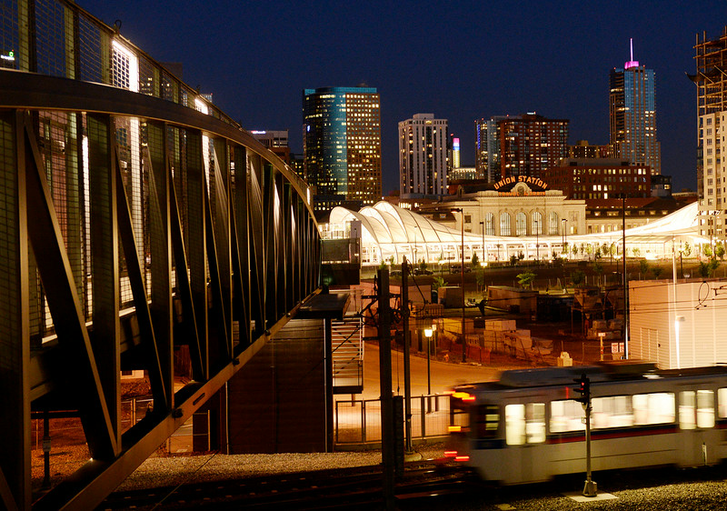 . Denver\'s Union Station is seen from a pedestrian bridge as a light rail train travels past. The station is  about to reopen with restaurants and a hotel. The space is now a downtown transit center, with trains, buses and light rail connections. It was photographed on Monday, June 9, 2014. (Denver Post Photo by Cyrus McCrimmon)