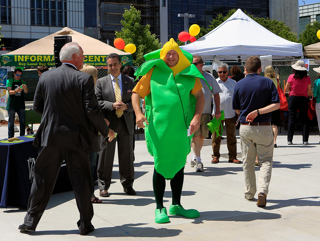 . At center, Chris Wilder, Executive Director of the Valley Medical Center Foundation, dressed as a corn stalk at the new Santa Clara Valley Medical Center Farmer\'s Market in San Jose, Calif. on Wednesday, May 15, 2013.  (LiPo Ching/Bay Area News Group)