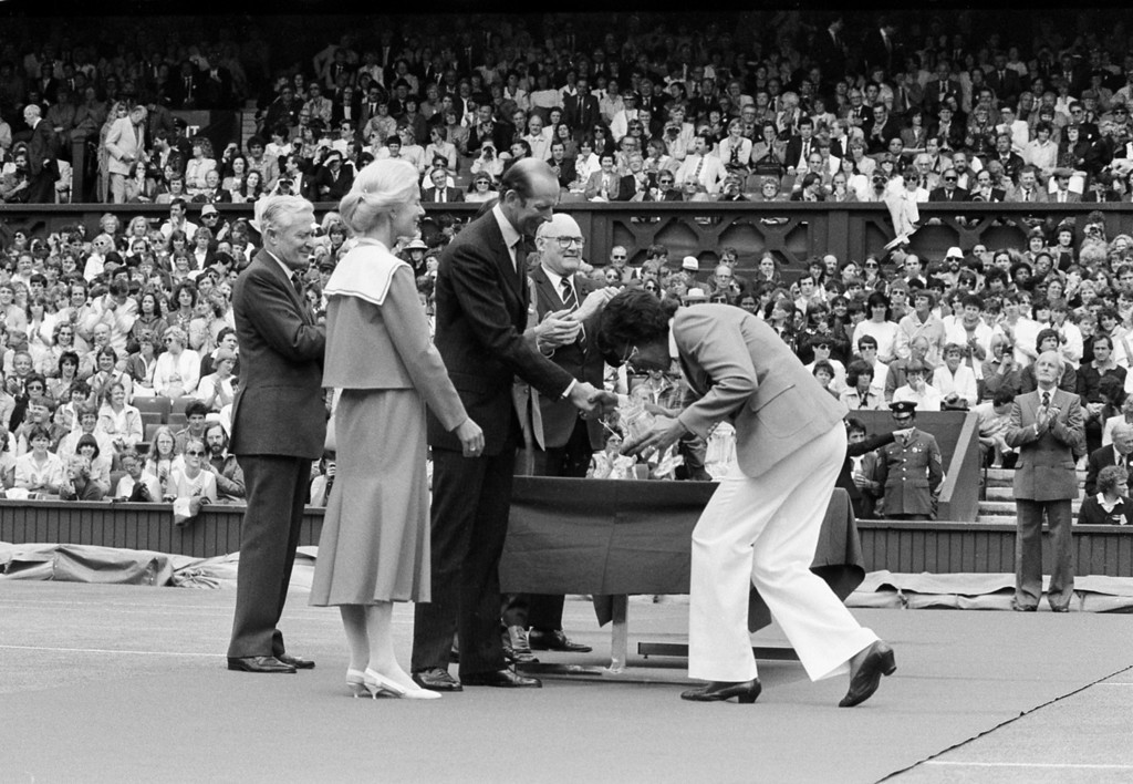 . Althea Gibson, of United States, curtsies before the Duke of Kent, president of the All England Lawn Tennis Club, on Center Court during a ceremony to mark the centennial year of the Ladies\' Championships at Wimbledon, England, July 2, 1984.  Gibson, a former professional golfer, became the first black person to win the Wimbledon title in 1957.  Standing second from left is the Duchess of Kent.  (AP Photo)