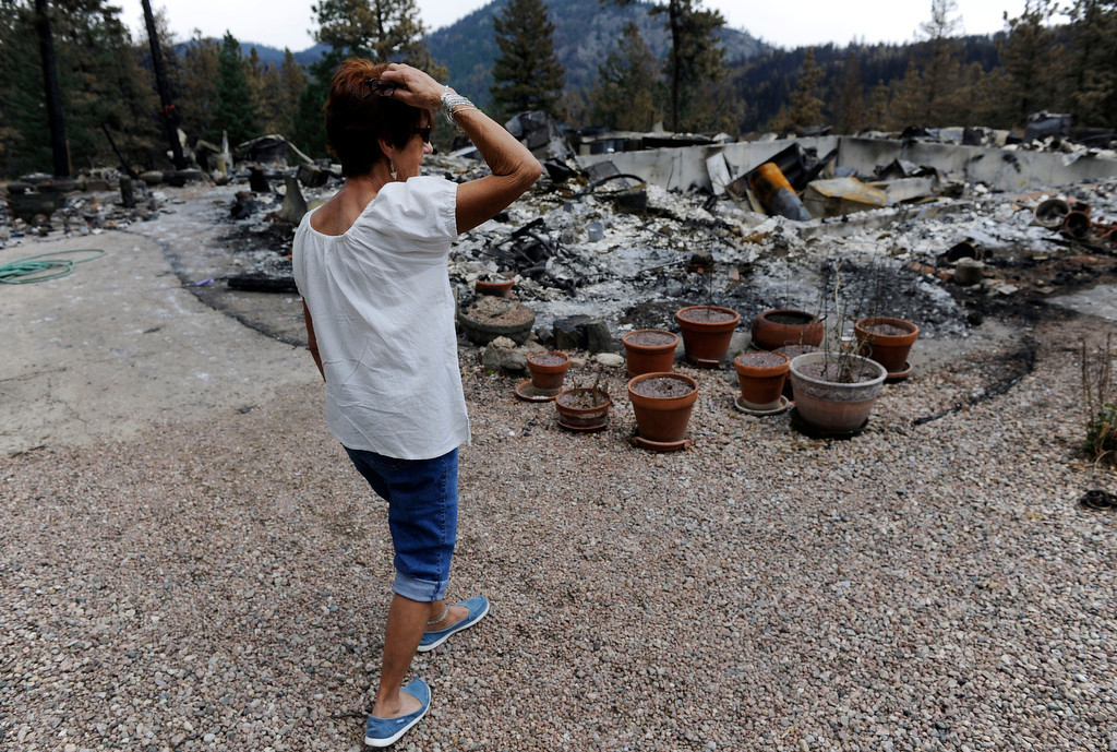 . Pat Baker surveys the burned out shell of her house Friday afternoon in Rist Canyon near Davis Ranch Rd. and Desillio Rd. west of Ft. Collins. Baker\'s two-story house that she had lived in for 43 years, burned to the ground by the High Park Fire, the fire skipped past several out buildings and missed her neighbors house completely.  Andy Cross, The Denver Post
