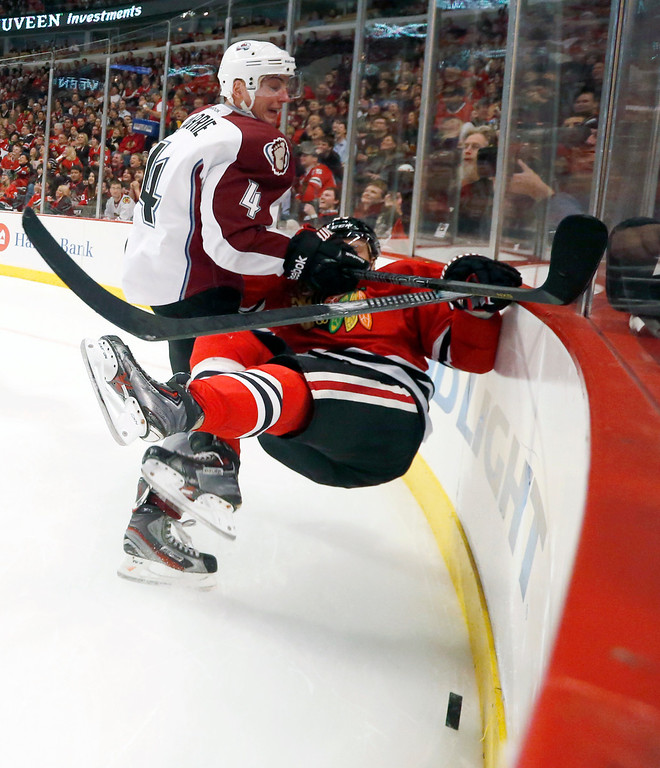 . Colorado Avalanche defenseman Tyson Barrie (4) checks Chicago Blackhawks right wing Kris Versteeg along the boards during the second period of an NHL hockey game Friday, Dec. 27, 2013, in Chicago. (AP Photo/Charles Rex Arbogast)