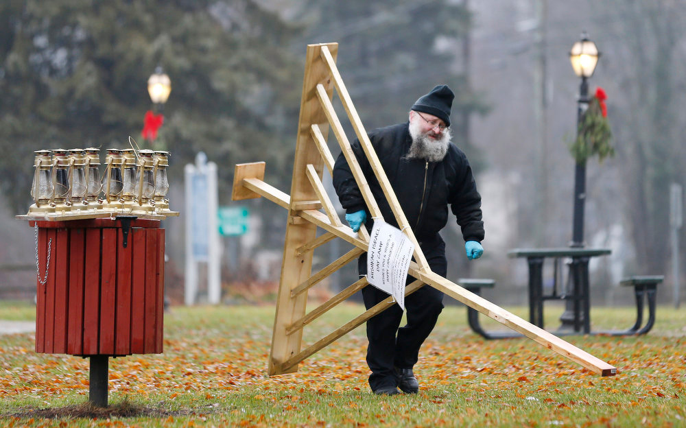 Description of . Rabbi Joseph Stock breaks down a Menorah at the completion of Hanukkah in the town square area of Monroe, Conn., where shooting victim Noah Pozner will be buried later in the day, Monday, Dec. 17, 2012. Stock will attend the burial services for the 6-year-old at B'nai Israel Cemetery. On Friday, gunman Adam Lanza killed his mother at their home and then opened fire inside the Sandy Hook Elementary School in Newtown, killing 26 people, including 20 children. (AP Photo/Julio Cortez)