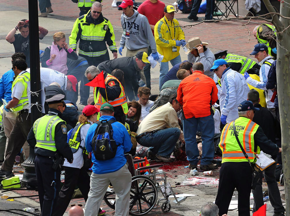 . Medical workers aid injured people at the 2013 Boston Marathon following an explosion in Boston, Monday, April 15, 2013. Two explosions shattered the euphoria of the Boston Marathon finish line on Monday, sending authorities out on the course to carry off the injured while the stragglers were rerouted away from the smoking site of the blasts. (AP Photo/The Boston Globe, David L Ryan)