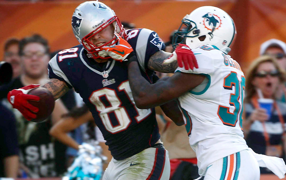 . Miami Dolphins strong safety Chris Clemons (30) grabs New England Patriots tight end Aaron Hernandez (81) face mask during the second half of an NFL football game on Sunday, Dec. 2, 2012, in Miami. (AP Photo/John Bazemore)